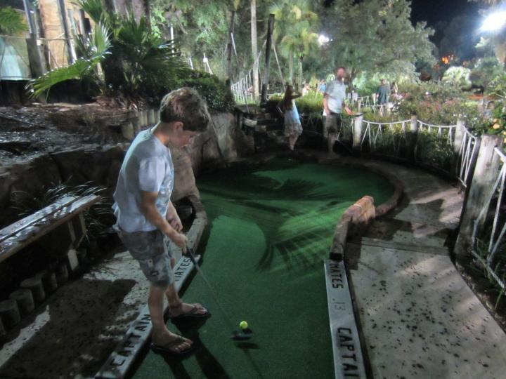 Kind spielt Minigolf im Pirates Cove Adventure Golf in Orlando, Florida