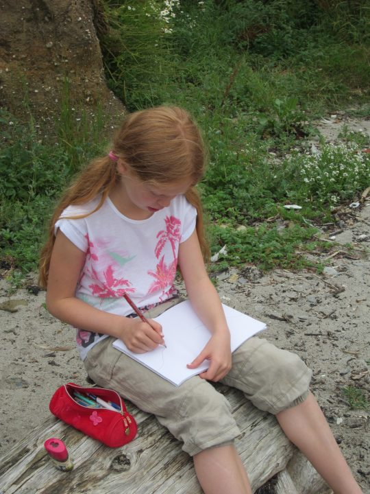 Kind malt am Strand in Cornwall